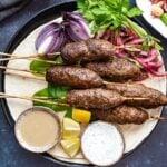 Kofta kebab served on lavash with sumac onions, tahini sauce and yogurt sauce.