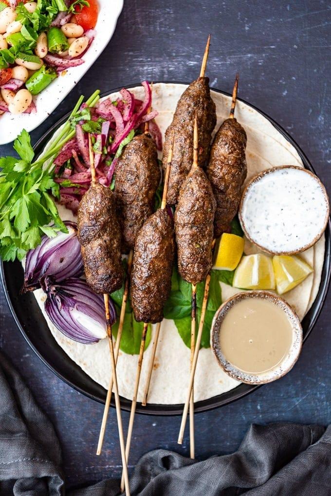 Kofta kebab served on lavash with sumac onions, tahini sauce and yogurt sauce on the side.