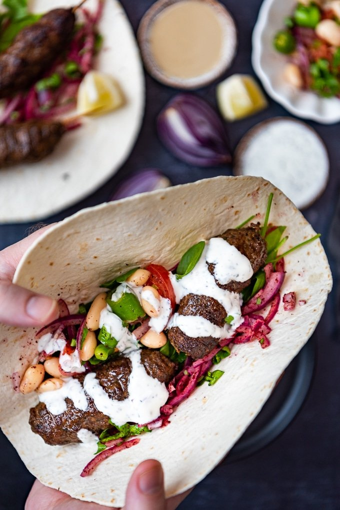 lamb and beef kofta skewers in a wrap with yogurt sauce