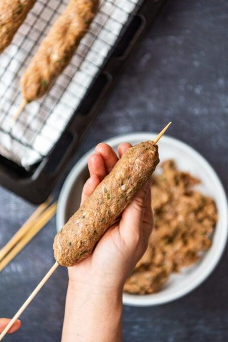moulding kofta kebab mixture on wooden skewers