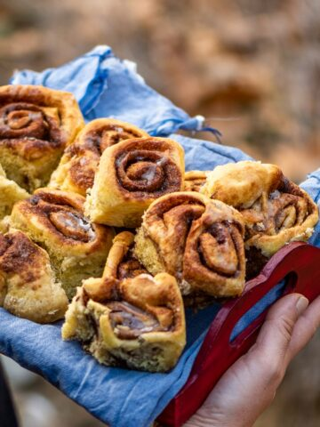 Hands holding cinnamon pumpkin rolls in a wooden tray lined with a denim fabric.