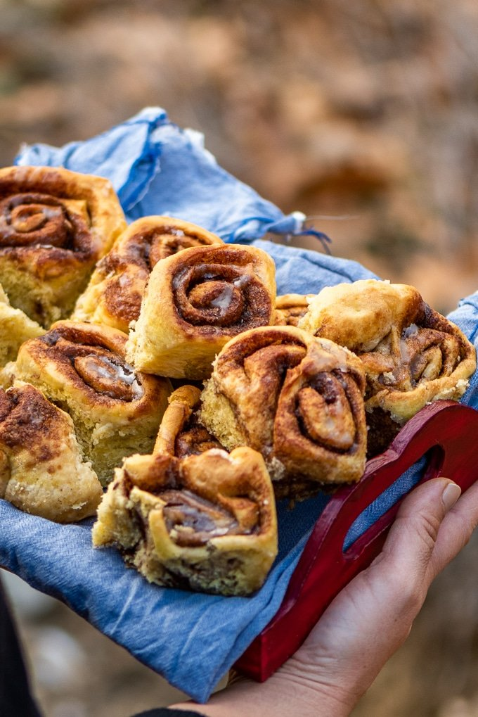 Holding pumpkin cinnamon rolls in a small wooden serving tray.