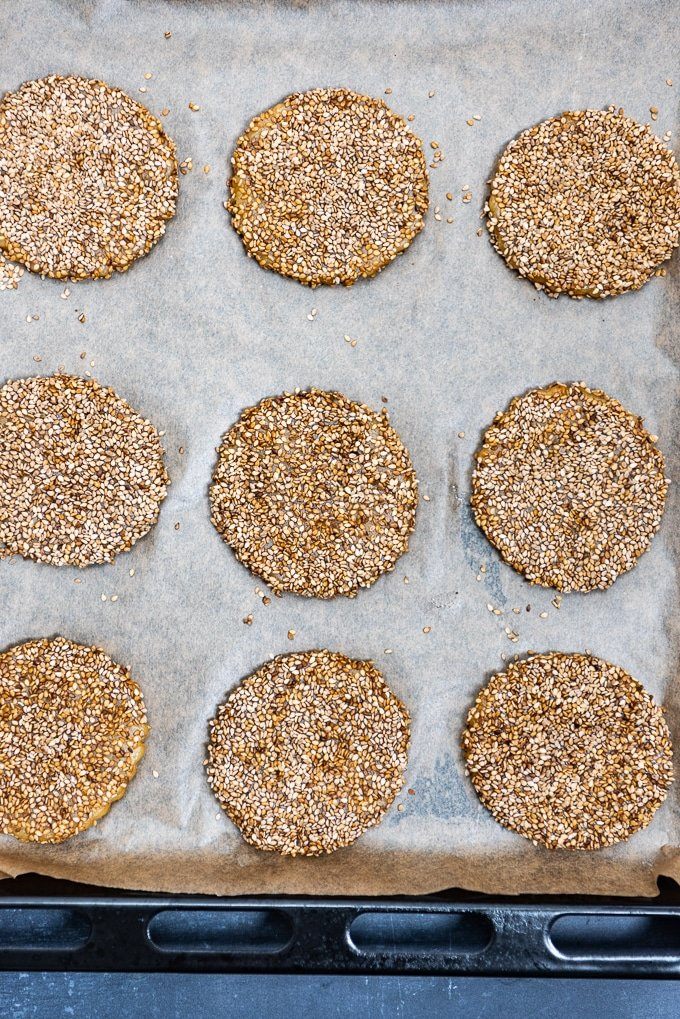 Tahini cookies coated well with sesame seeds on a baking sheet.