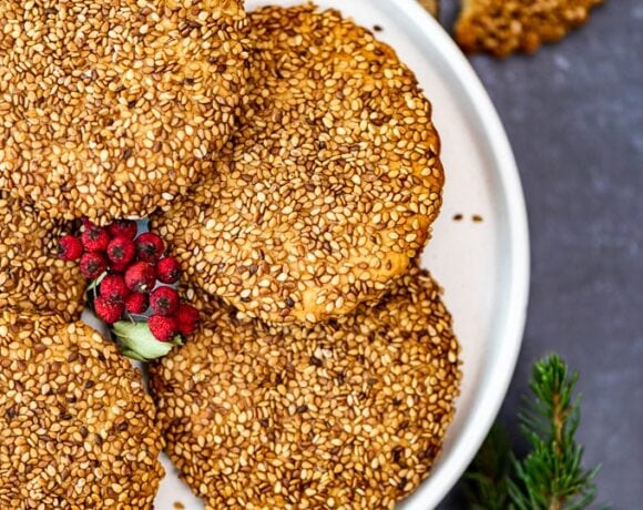 Turkish tahini sesame cookies on a white plate, holly berries in the middle and pine branch on the side.