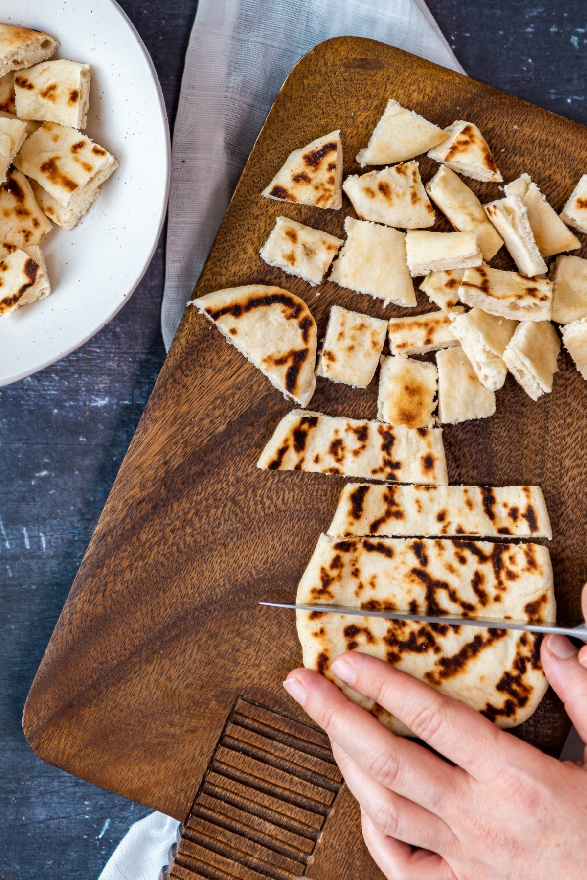 Hands cutting pide bread into chunks on a wooden board.