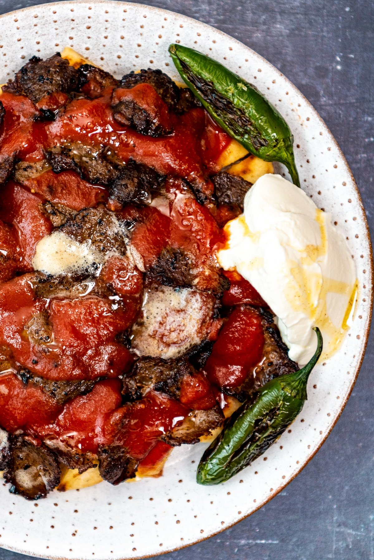 Homemade Iskender kebab served with tomato sauce, green peppers and yogurt on a plate.