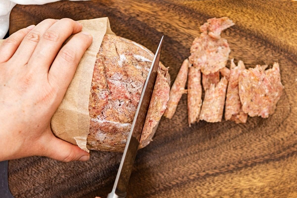 Hands slicing frozen ground beef log.