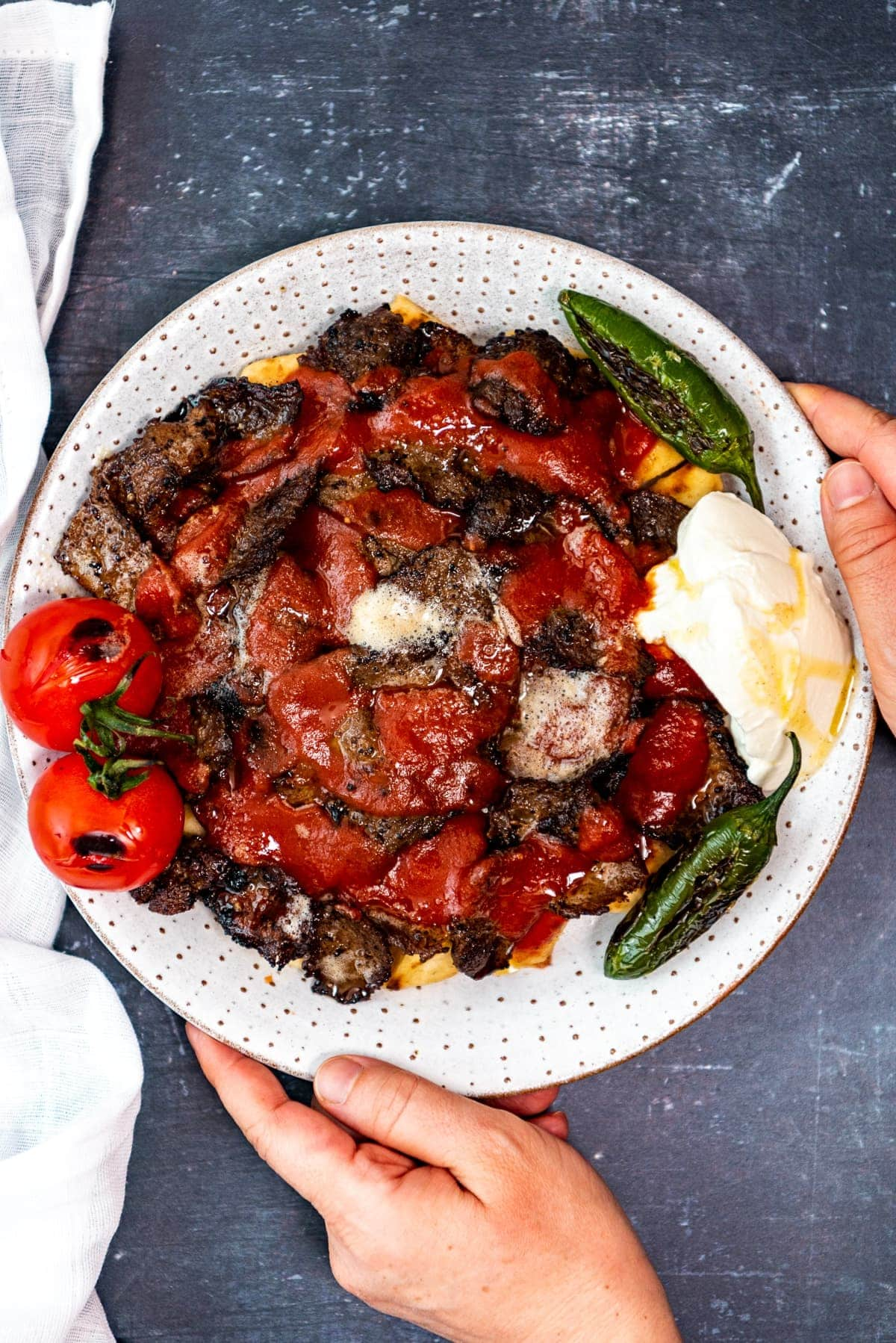 Hands holding a white plate with homemade iskender kebab with pide bread, tomato sauce, browned butter, yogurt, roasted tomatoes and green peppers.