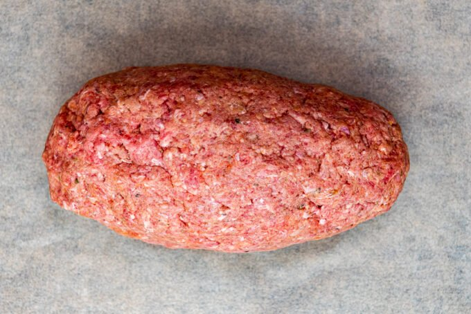 A log of ground beef mixture on a piece of baking paper.
