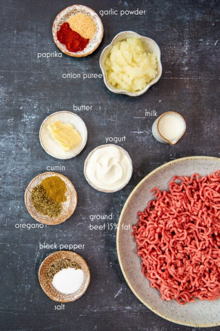 Ground beef, pureed onion, yogurt, milk and spices in separate bowls on a dark background.