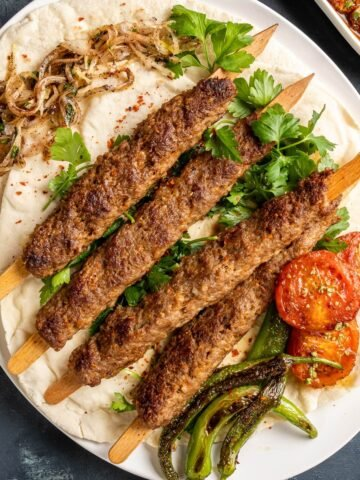 Adana kebab skewers on lavash with parsley, roasted tomatoes and green peppers.