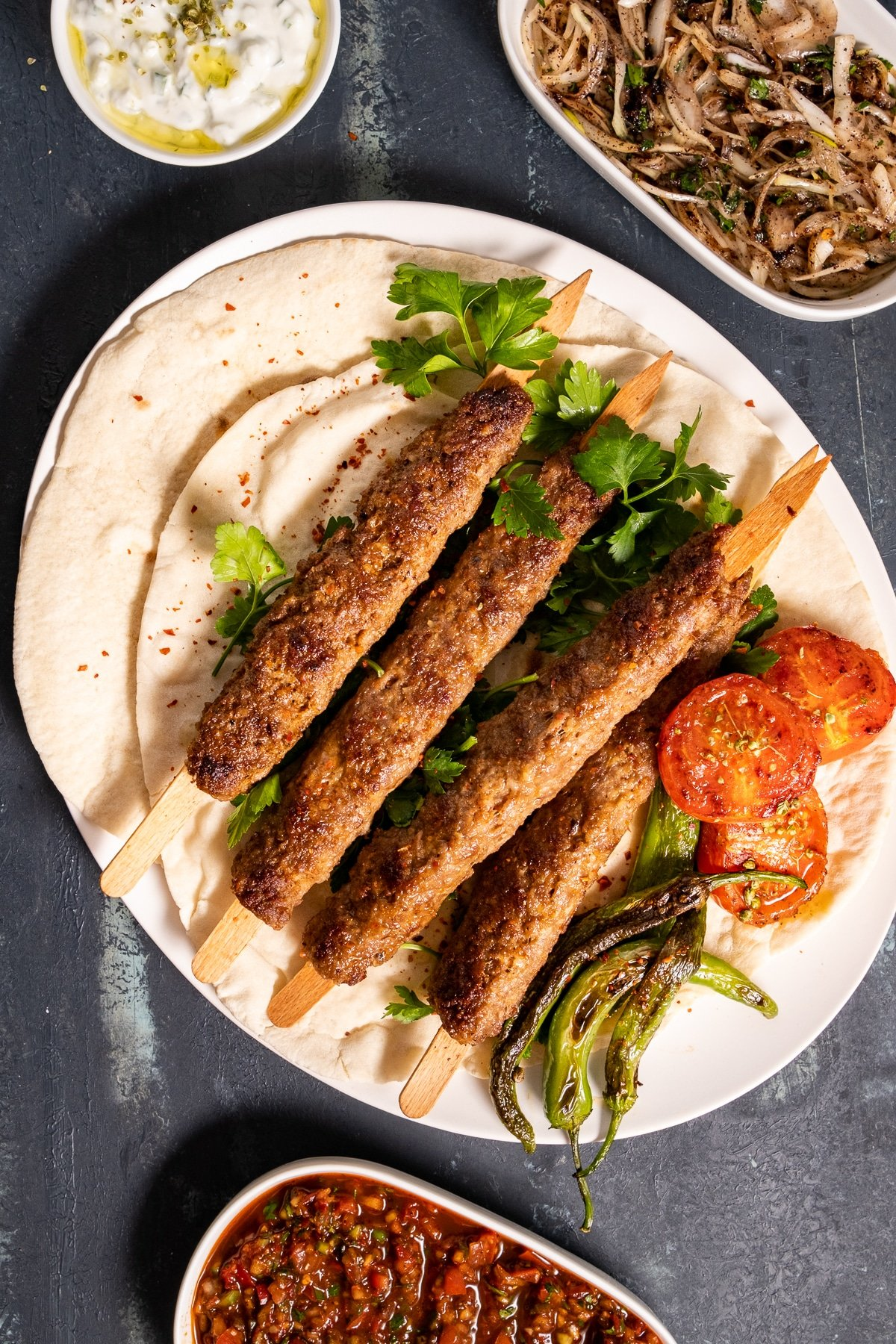 Ground lamb kebabs served on lavash with roasted tomatoes and green peppers on a white plate, ezme and sumac onions on the side.