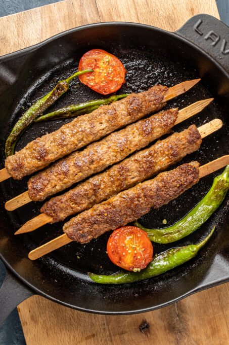 Minced lamb kebabs in an iron skillet and tomatoes and green peppers inside it.