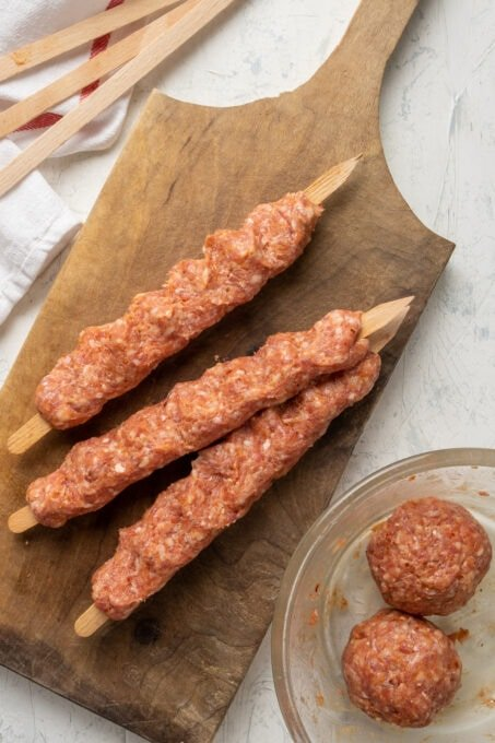 Spicy ground lamb mixture shaped on three wooden skewers on a wooden cutting board and two large balls of meat in a bowl on the side.