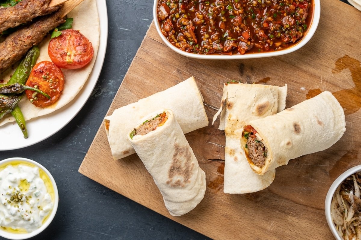 Lamb mince kebab dürüm wraps on a wooden board and ezme and cacik on the side.