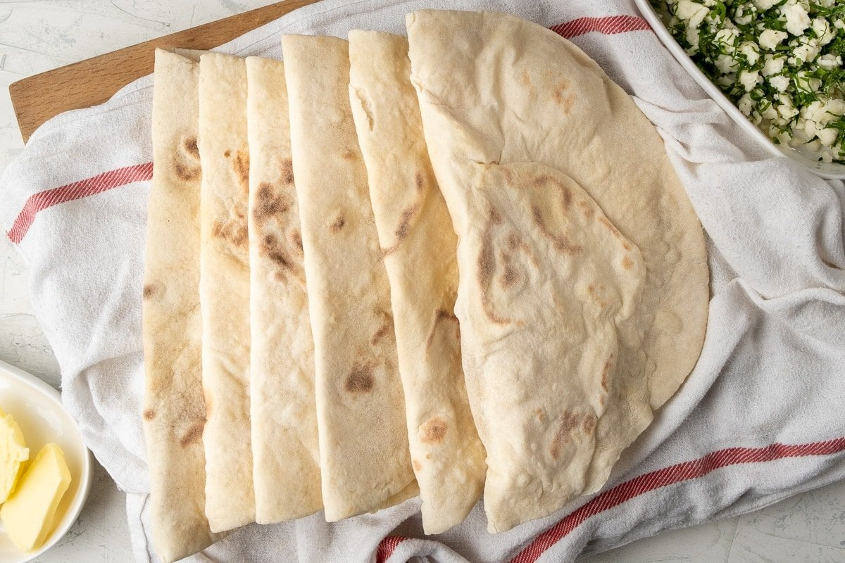 Lavash flat breads on a white kitchen towel and some butter in a small oval bowl on one side and feta parsley mixture in another oval bowl on the other side of the breads.