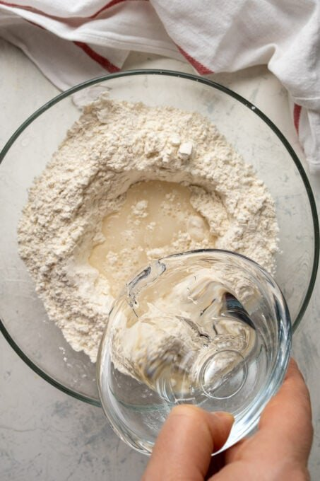 A hand pouring water into the flour mixture in a glass mixing bowl.