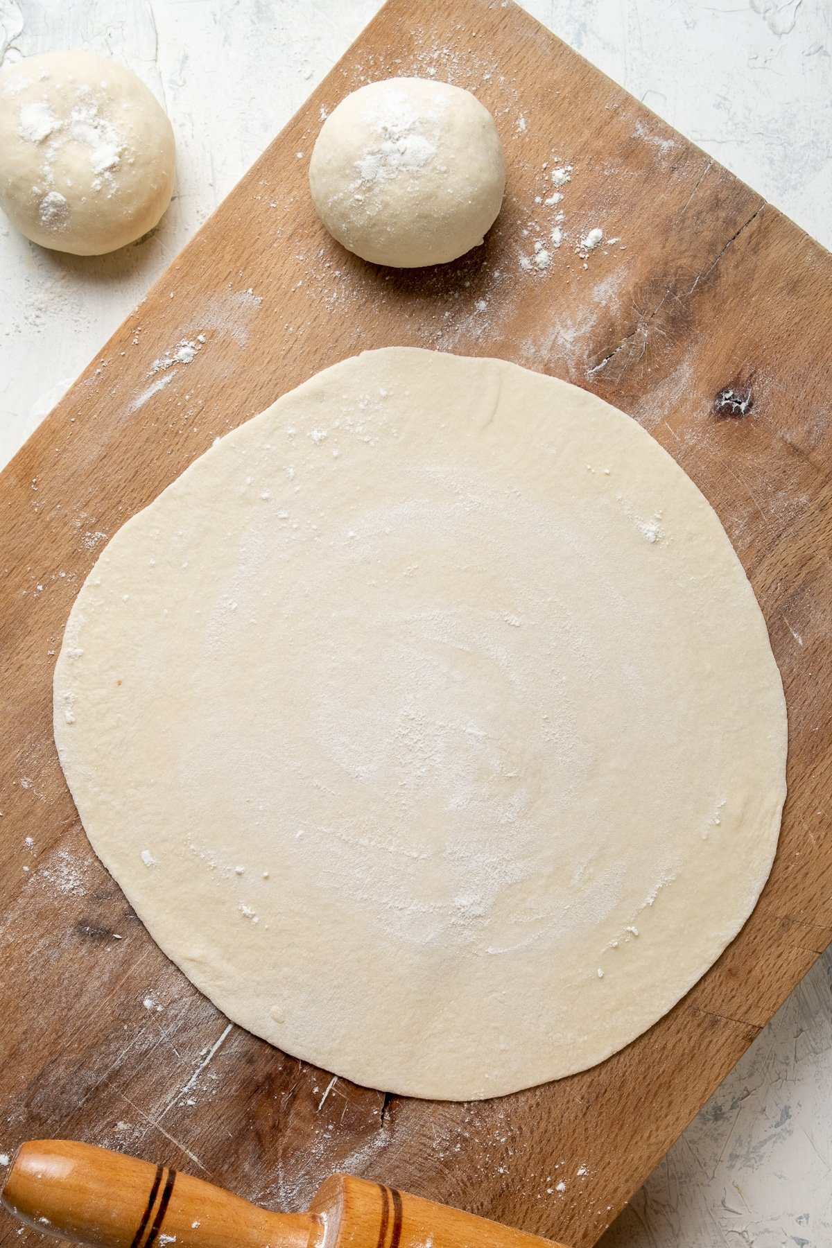 Rolled out dough on a wooden board and two dough balls on the side.