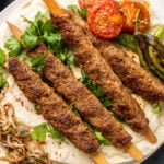 Adana kebabs served with roasted tomatoes and peppers, parsley and sumac onions on a lavash bread.