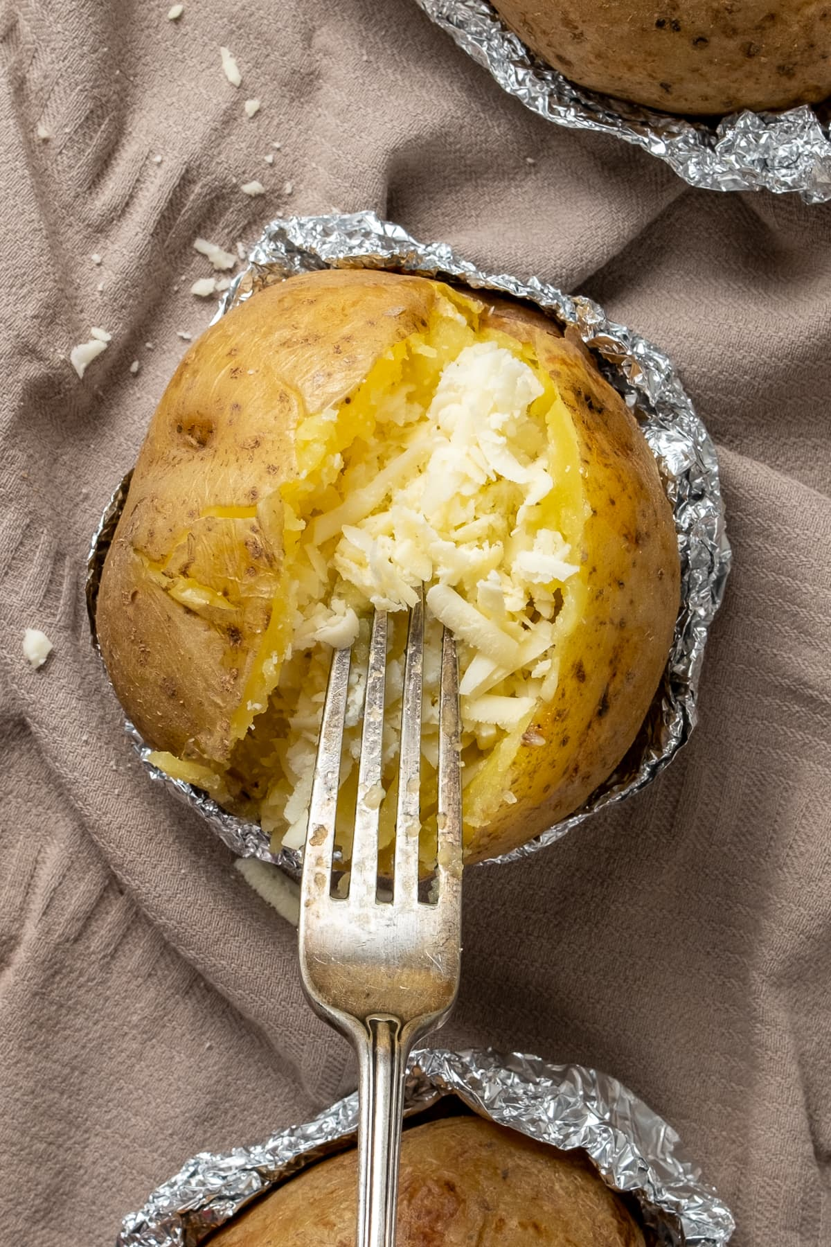 Adding cheese into a baked potato and a fork inside it.