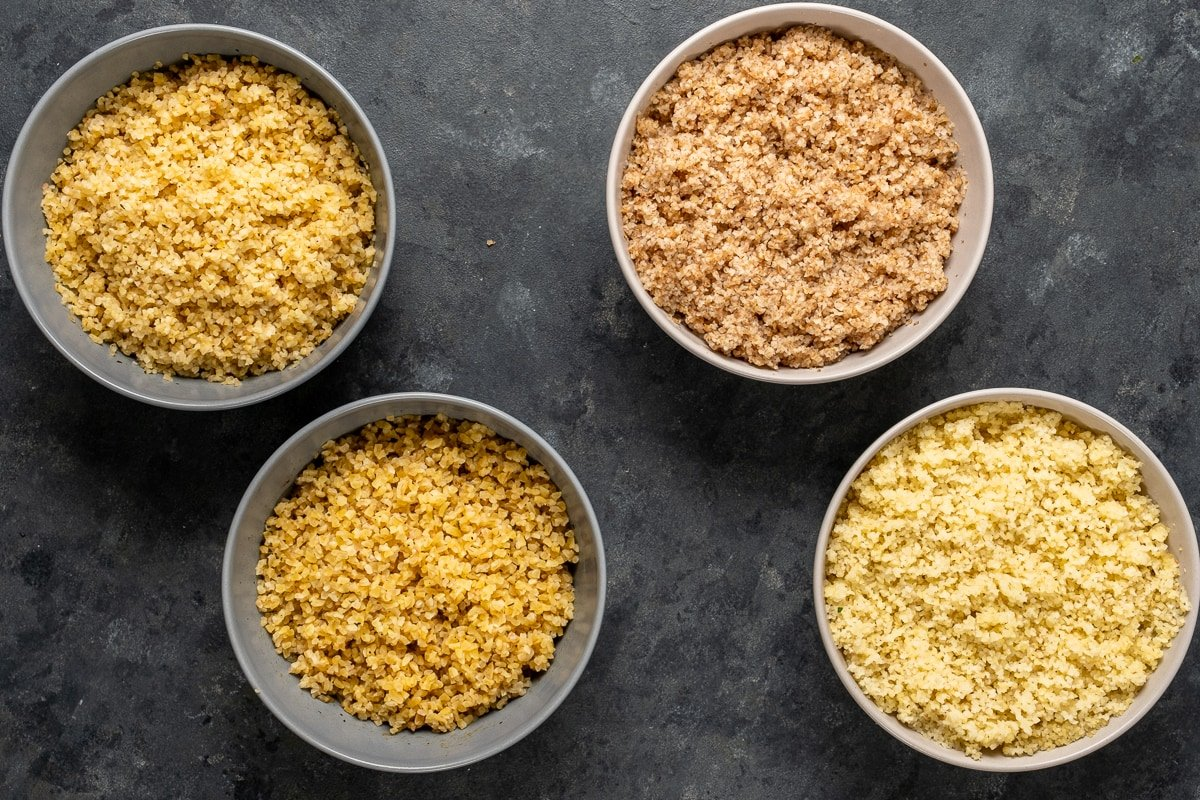 Two bowls of fine bulgur and two bowls of medium bulgur on a dark background.