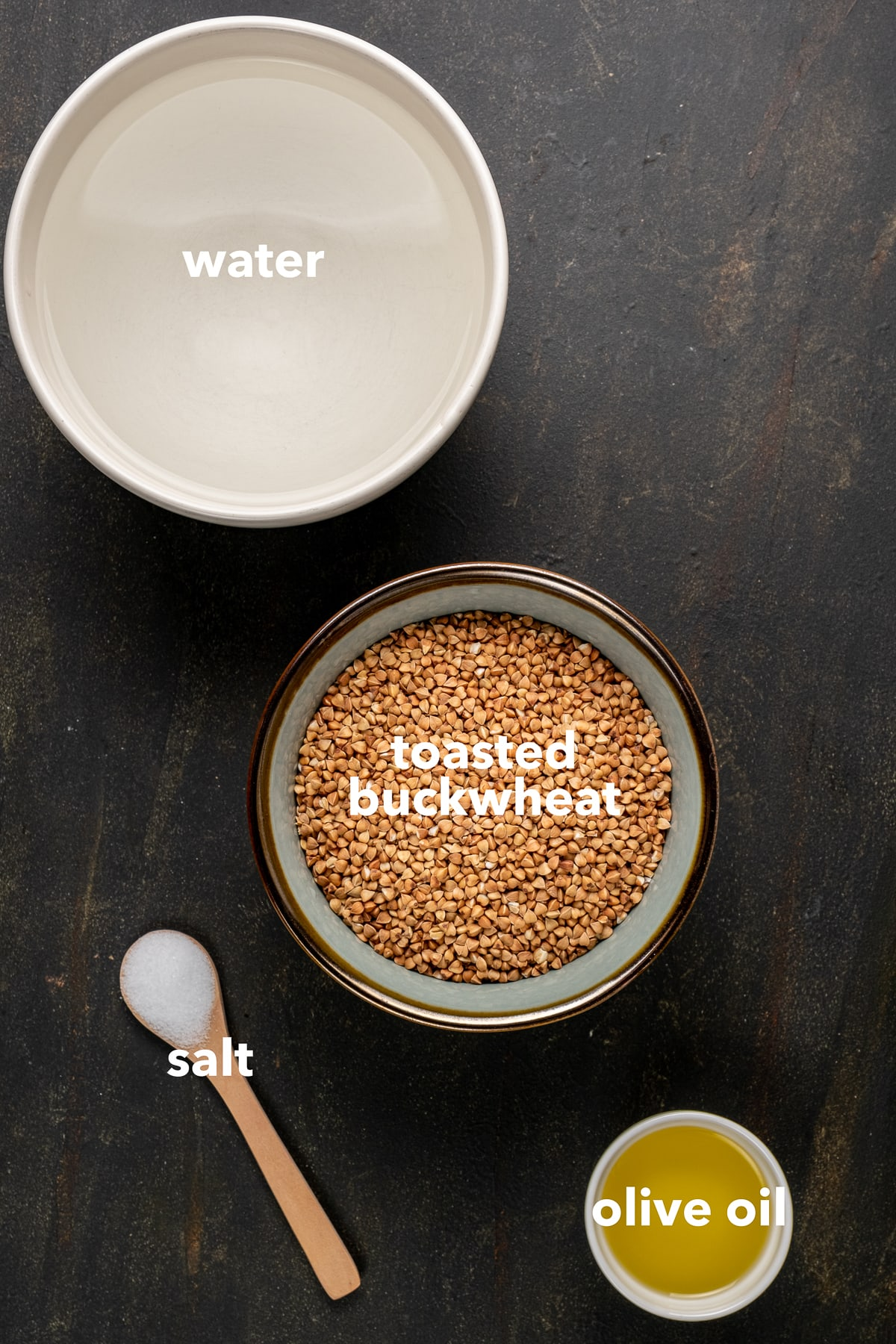 Toasted buckwheat, water, olive oil in bowls and salt in a small wooden spoon