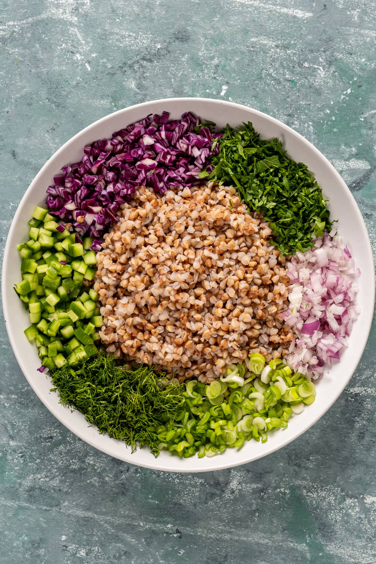 Cooked buckwheat, finely chopped red onion, red cabbage, parsley, fresh dill, green onions and cucumbers all in a white salad bowl.