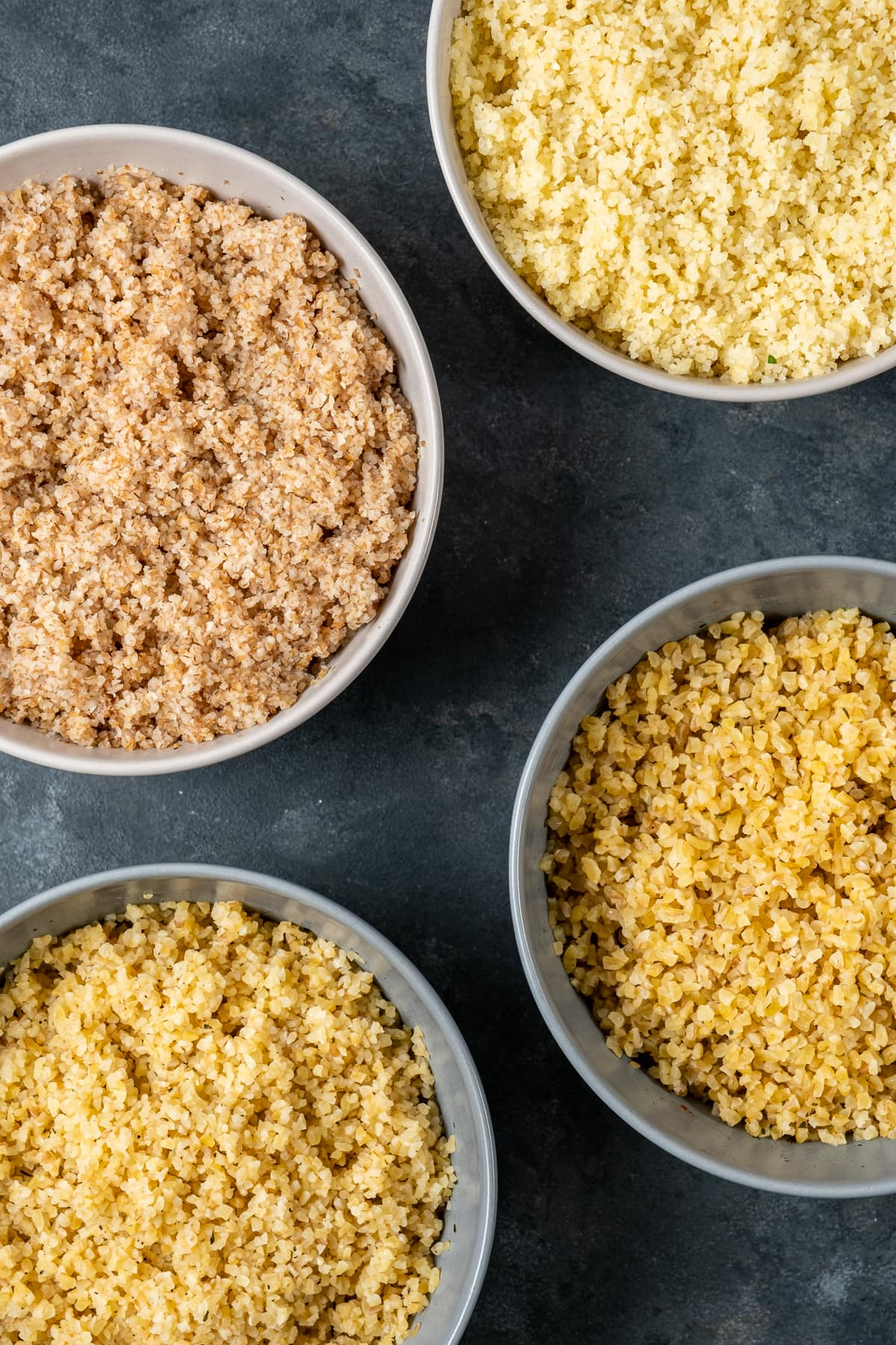Fine bulgur and medium bulgur after soaked in four different bowls on a dark background.
