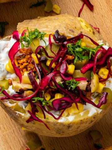 Turkish kumpir topped with red cabbage, corn, olives, Russian salad and bulgur salad.