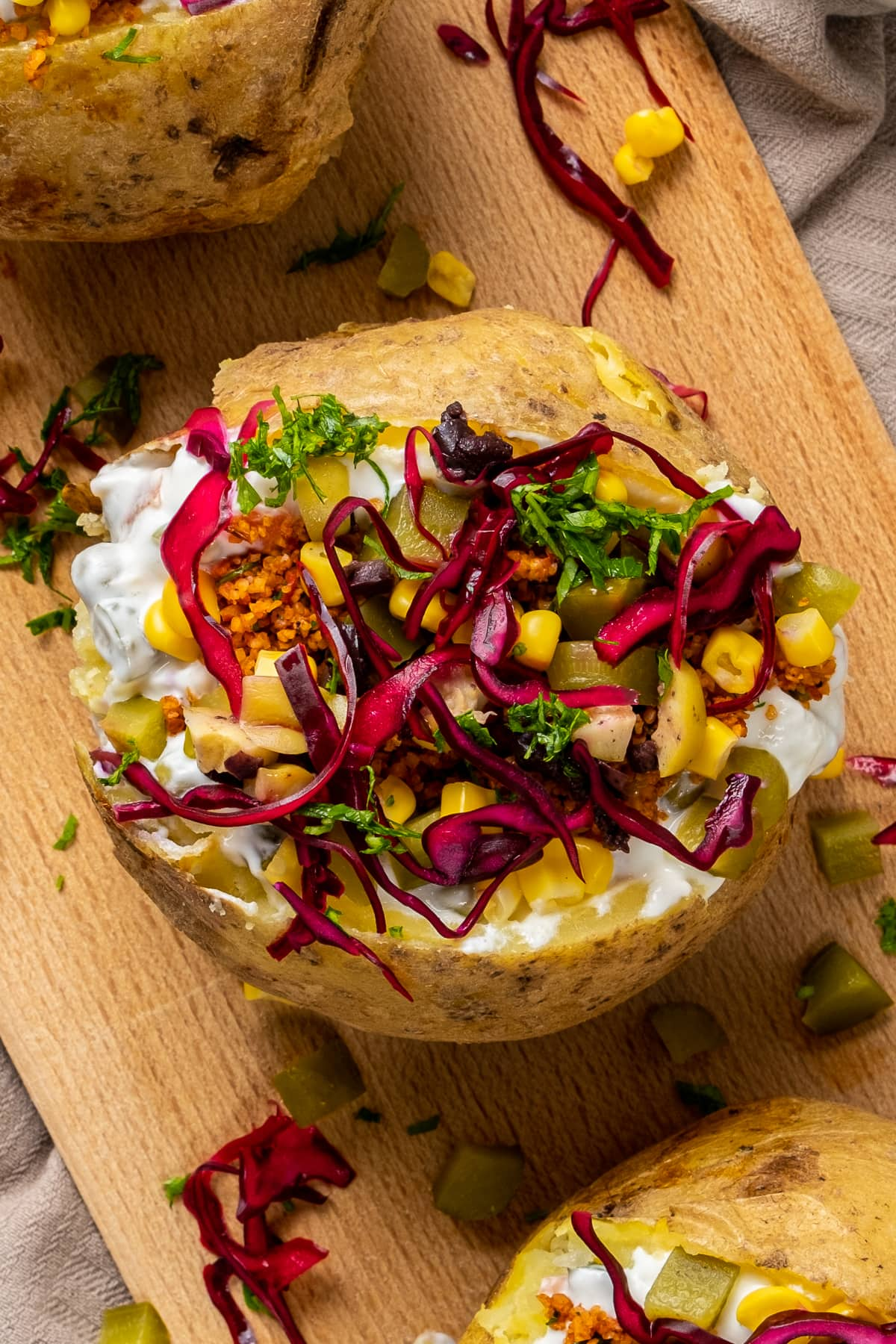 Kumpir loaded with bulgur salad kisir, corn, olives, dill pickles and red cabbage on a wooden board.