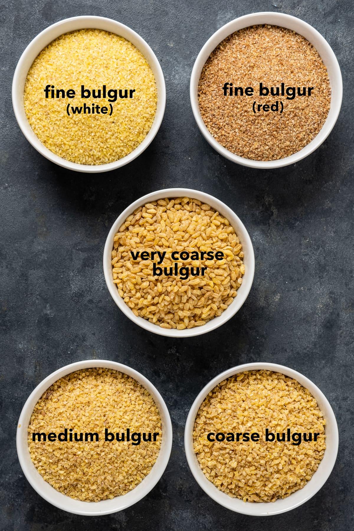 White fine bulgur, red fine bulgur, medium bulgur, coarse bulgur and very coarse bulgur in small bowls on a dark background.