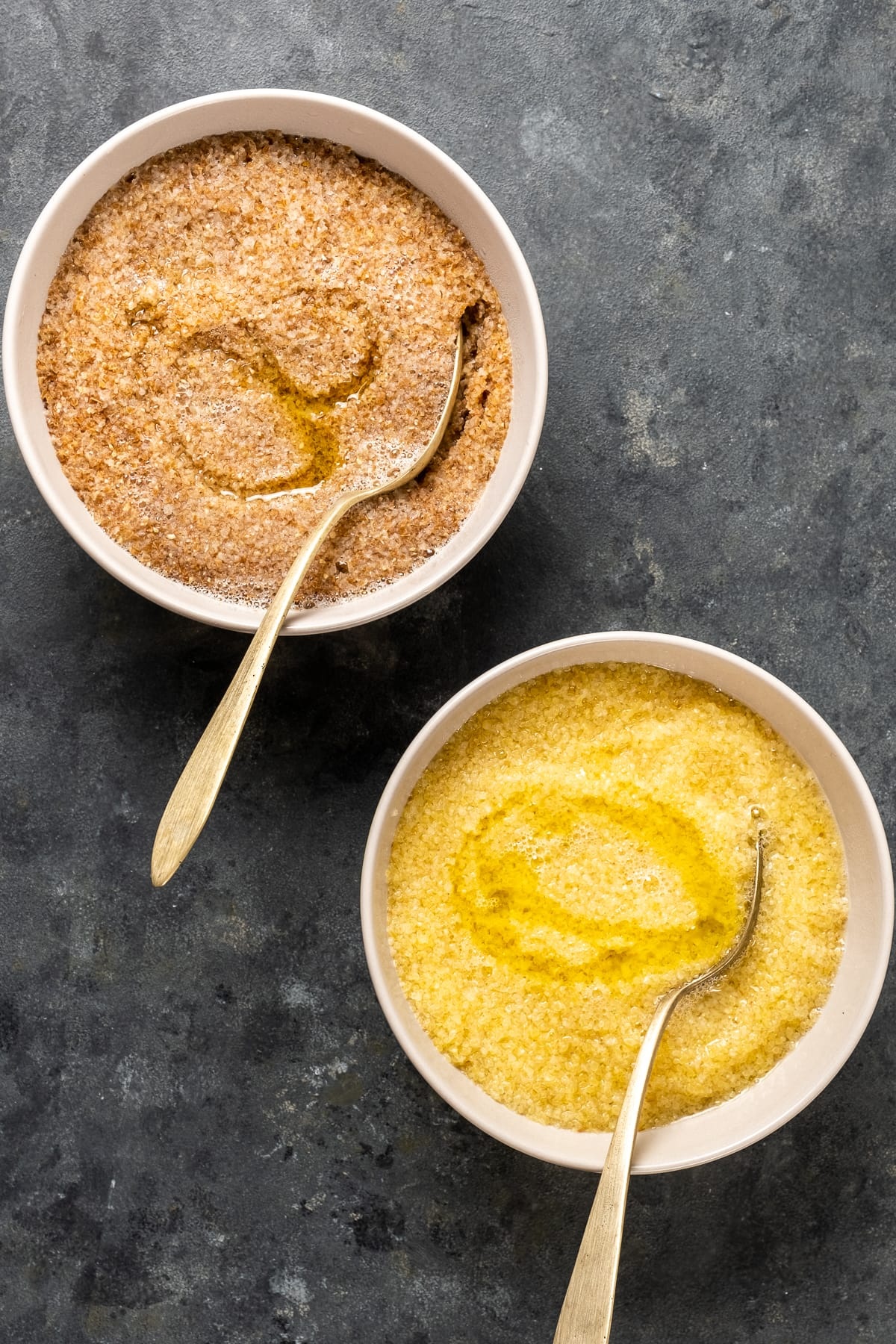 Red fine bulgur and white fine bulgur soaked in water and olive oil in two white bowls with spoons inside them.